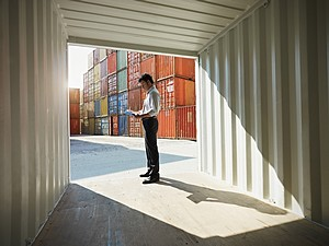 man standing in shipping and cargo container